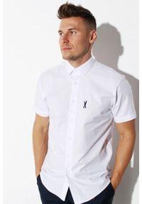 """Koszula Edward Orlovski Krótki Rękaw Biała """"Black"""". Typ kołnierza: kołnierzyk klasyczny. Kolor: biały. Materiał: bawełna, włókno. Długość rękawa: krótki rękaw. Długość: krótkie. Styl: elegancki"""